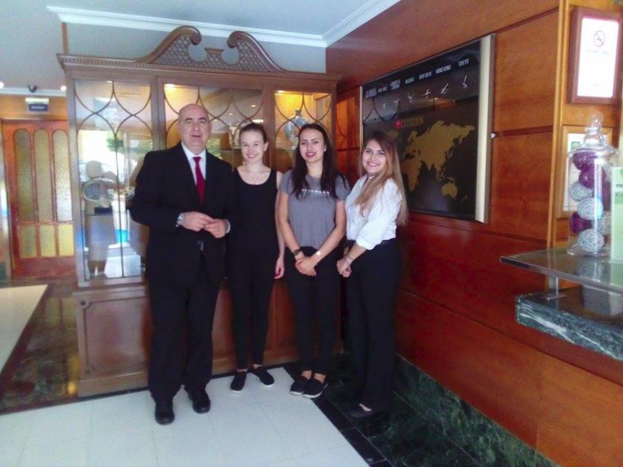 Grupa hotelarek ze swoim tutorem i właścicielem hotelu